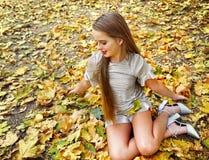 Sitzender Fall des Herbstmodekleiderkindermädchens verlässt Park im Freien stockfotos
