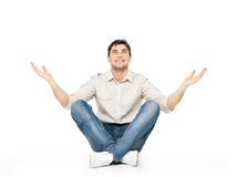 Sitzender glücklicher Mann mit den angehobenen Händen oben Stockfoto