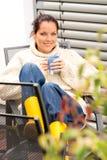 Sitzender Hinterhof des glücklichen entspannenden Schalen-Tees der Frau Stockfotografie