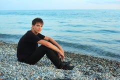 Sitzender Jugendlichjunge auf Steinseeküste Lizenzfreies Stockbild