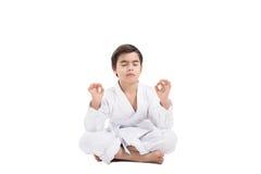 Sitzender Junge in einem Kimono ist und Konzentration entspannend stockfotografie