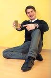 Sitzender junger Mann, der am Telefon zeigt stockbilder