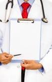 Sitzender männlicher Doktor, der ein leeres Klemmbrett hält stockbilder