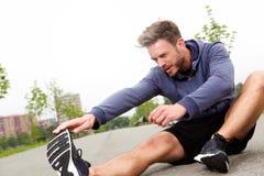 Sitzender männlicher Läufer, der Ausdehnung tut stockbilder