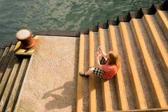 Sitzender Mann, der Fotos auf einem Pier macht lizenzfreies stockfoto