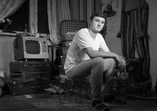 Sitzender Mann an der Rumpelkammer, die Kamera betrachtet Lizenzfreie Stockbilder