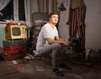 Sitzender Mann an der Rumpelkammer, die Kamera betrachtet Stockfotos