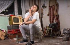 Sitzender Mann, der seinen Hals an der Rumpelkammer verkratzt lizenzfreie stockfotografie