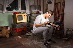 Sitzender Mann, der unbenutzten Kessel an der Rumpelkammer hält Lizenzfreie Stockfotografie