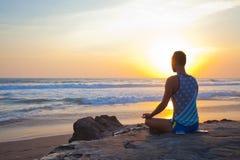 Sitzender Mann, der Yoga auf Ufer von Ozean tut lizenzfreies stockfoto