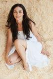 Sitzender Sand der Portraitfrau Stockfoto
