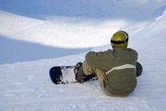 Sitzender Snowboarder auf Steigung Stockfotos