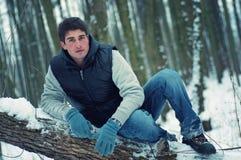 Sitzender stattlicher junger Mann auf Baum stockfotografie