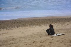 Sitzender Surfer auf dem Strand stockbilder