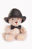Sitzender Teddybär mit Querbinder und Hut Stockfotografie