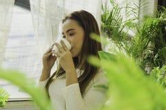 Sitzender trinkender Kaffee der Schönheit am Fensterhaus, Sonnenlichtmorgen, mit entspanntem und ruhigem Gefühl an einem entspann lizenzfreie stockfotos