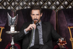 Sitzender und Inhalierung shisha Mann im Restaurant lizenzfreie stockfotos