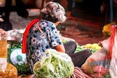 Sitzender Verkäufer in einem asiatischen Markt Stockfoto