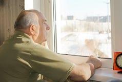 Sitzendes Anstarren des älteren Mannes aus einem Fenster heraus lizenzfreie stockfotografie