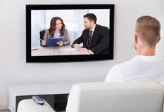 Sitzendes aufpassendes Fernsehen des Mannes zu Hause Lizenzfreie Stockfotografie
