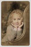Sitzendes Blicken des netten kleinen blonden Mädchens über Seitenlehnen Lizenzfreie Stockbilder