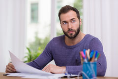 Sitzendes Denken des Mannes an seinem Schreibtisch Stockbild