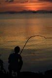 Sitzendes Fischen des Mannes bei Sonnenuntergang Stockfotos