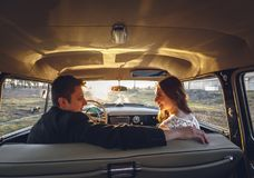 Sitzendes Lächeln der jungen Hochzeitspaare innerhalb des Retro- Autos und Betrachten einander gerade umarmt verheiratete Umarmun Lizenzfreie Stockfotos