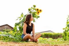 Sitzendes Lachen der jungen Frau unter einer Sonnenblume im Sonnenlicht stockfotografie