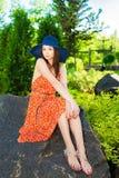 Sitzendes Mädchen auf dem Stein Stockbilder