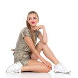 Sitzendes Mädchen, das über Schulter schaut Stockbild