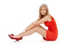 Sitzendes Mädchen im roten Kleid Stockfoto
