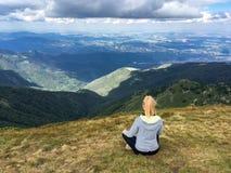 Sitzendes meditieren der jungen blonden Frau ein Bergblick Stockfoto