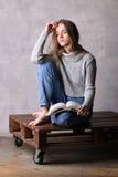 Sitzendes Modell, das ein Buch hält Grauer Hintergrund Lizenzfreie Stockfotografie