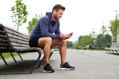 Sitzendes Musik draußen hören des älteren Athleten Lizenzfreies Stockfoto