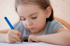 Sitzendes Schreiben des Babys am Tisch Stockbild