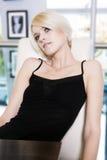 Sitzendes Träumen der recht jungen blonden Frau Stockbild