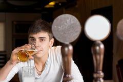 Sitzendes Trinken des Mannes an einer Kneipe Lizenzfreies Stockbild