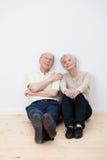 Sitzendes Träumen der älteren Paare in einem neuen Haus Stockfotografie