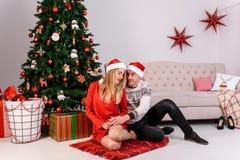 Sitzendes Umarmen des Mannes und der Frau nahe Weihnachtsbaum Lizenzfreies Stockbild
