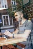 Sitzendes und denkendes am Fenster schauen des Mannes Stockbild