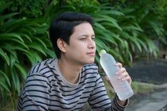 Sitzendes und Trinkwasser des asiatischen Mannes stockfoto