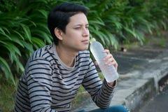 Sitzendes und Trinkwasser des asiatischen Mannes stockbild