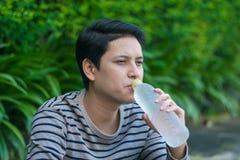 Sitzendes und Trinkwasser des asiatischen Mannes stockbilder