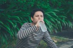 Sitzendes und Trinkwasser des asiatischen Mannes lizenzfreie stockfotos