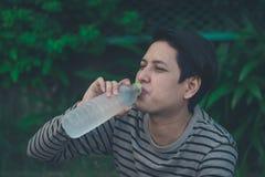 Sitzendes und Trinkwasser des asiatischen Mannes lizenzfreie stockbilder