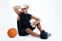 Sitzendes und Trinkwasser des müden Basketball-Spielers des jungen Mannes Lizenzfreies Stockbild
