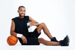 Sitzendes und Trinkwasser des netten Basketball-Spielers des jungen Mannes Lizenzfreie Stockfotos