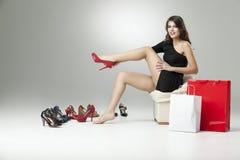 Sitzendes Versuchen der jungen Frau auf den Schuhen, die glücklich schauen Stockfoto
