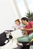 Sitzendes werfendes Geld des glücklichen Paars in der Luft Lizenzfreies Stockbild